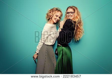 Two cheerful young women dressed in sweaters and skirts posing in the studio over blue background. Winter fashion.