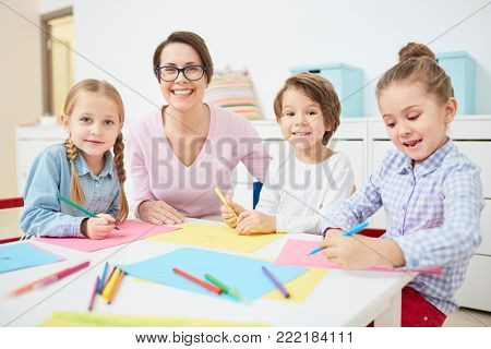 Happy young teacher and small group of adorable kids drawing with crayons in kindergarten
