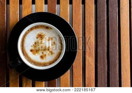 A Cup of Cappuccino Coffee on the horaizontal line brown wood table and ready to served and enjoy drink in the relaxing time with copy space.