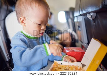 Cute little Asian 18 months / 1 year old toddler baby boy child wearing blue sweater eating food during flight on airplane. Flying with children, Happy air travel with kids & little traveler concept