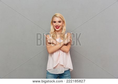 Portrait of a joyful girl standing and pointing two fingers both ways isolated over gray background