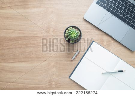 Minimal work space - Creative flat lay photo of workspace desk. Top view office desk with laptop, notebooks and plant copy space on wooden background. Top view with copy space, flat lay photography.