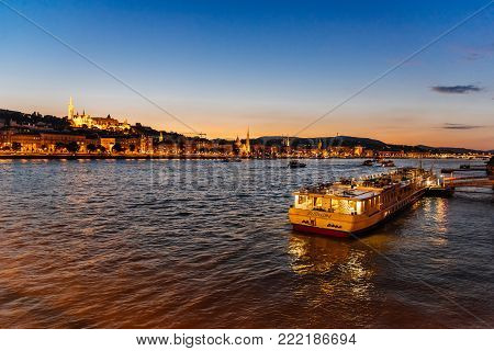 Budapest, Hungary - August 13, 2017:  Cruise ship for tourists moored in Danube river in Budapest against Buda Castle at sunset