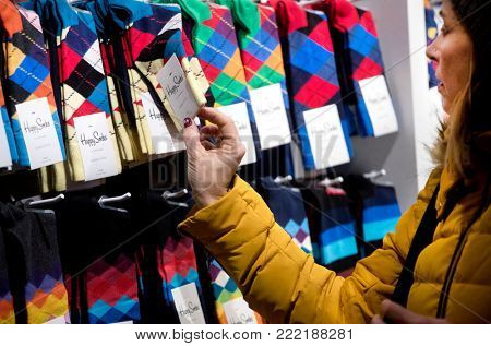BARCELONA, SPAIN - JANUARY, 3: Shopper watching socks and prices in clothing shop on city centre on January 3, 2018 in Barcelona, Spain