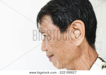 Close-up Senior Asian Man Ear Wearing  Hearing Aid of Audiphone, with smiling face, selective focus on ear, on white background