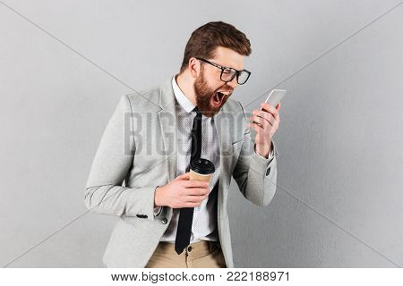 Portrait of a furious businessman dressed in suit and eyeglasses yelling at mobile phone while standing and holding coffee cup isolated over gray background