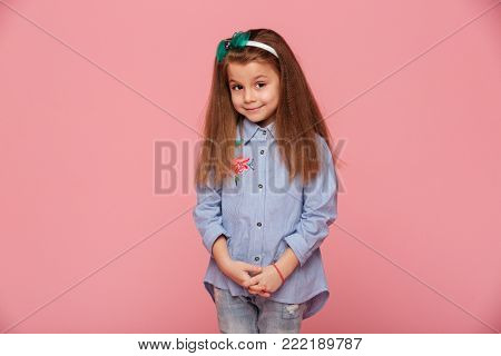 Portrait of cute schoolgirl 5-6 years having long auburn hair looking on camera with kind smile, isolated over pink background