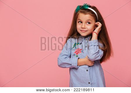 Portrait of cute schoolgirl 5-6 years touching her long auburn hair with kind lovely smile, isolated over pink background