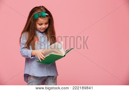 Image of smart schoolgirl 5-6 years with long auburn hair, reading interesting book isolated over pink background