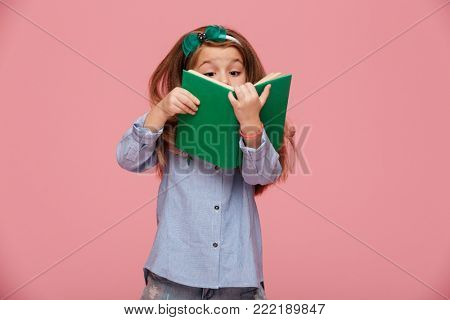 Image of amusing girl 5-6 years with long auburn hair reading interesting book, having fun isolated over pink background