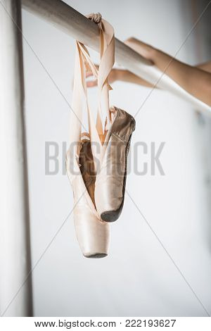 Close up view of pointes for ballet on barre and hands of ballerina in classroom