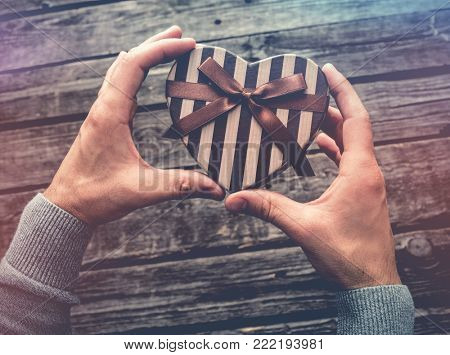 Heart shaped gift box in man's hands. Top view.