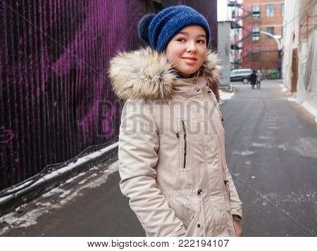 Happy teenage girl in winter jacket and knitted cap on the street close-up portrait