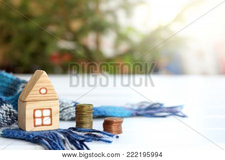 wooden house with a warm scarf next to a pile of coins / inexpensive cozy accommodation