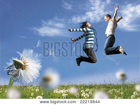 pareja divirtiéndose en una pradera llena de dientes de León