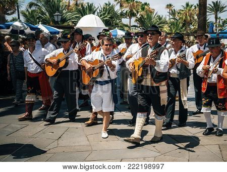 Puerto de la Cruz, Tenerife, Canary Islands - May 30, 2017: Canaries people dressed in traditional clothes walk along the street, sign and play guitars. Local residents of Tenerife celebrate the Day of the Canary Islands.
