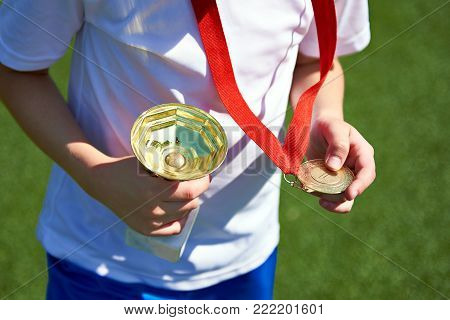 Winner boy sportsman with cup and gold medal