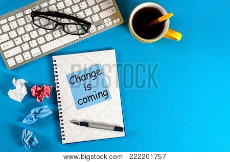 change is coming text write on notepad at workplace at blue background. Empty space for text and mockup.