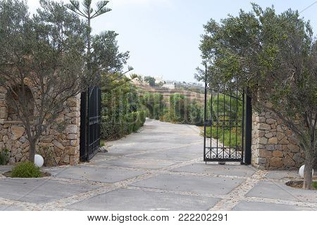 Park Entry With Open Wrought-iron Gate In Gradient Back And Shut Off The Track