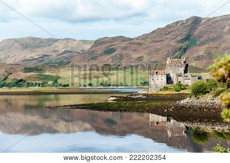 Majestic castle at Eilean Donan reflected in the high tide on Loch Alsh with sunny mountains and blue sky on background. Summertime outdoors horizontal image.