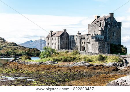 Majestic castle at Eilean Donan on Loch Alsh rock with sunny mountains and blue sky on background. Summertime outdoors horizontal image.
