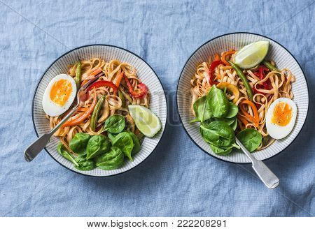 Yaki Udon noodles with stir fry vegetables, boiled egg and spinach. Vegetarian noodles with green beans, sweet peppers, mushrooms, carrots - healthy foods for lunch on a blue background, top view