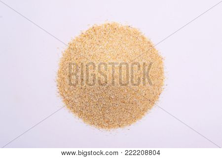 A pile of granulated garlic powder isolated on white background