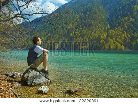 A man on the bank of a lake is enjoying the sun. The unique keyword for this collection is: lake77