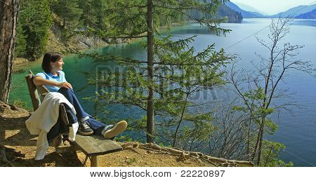 woman sitting on a bank beside a lake. The unique keyword for this collection is: lake77