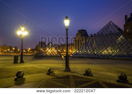 PARIS, FRANCE - DECEMBER 02, 2017: View of famous Louvre Museum with Louvre Pyramid at night. Louvre Museum is one of the largest and most visited museums worldwide