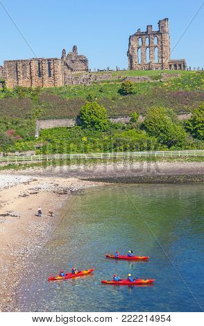 TYNEMOUTH, ENGLAND - MAY 28, 2012: Three kayakers set out in front of the ruins of Tynemouth Castle and Priory on the coast of North East England.