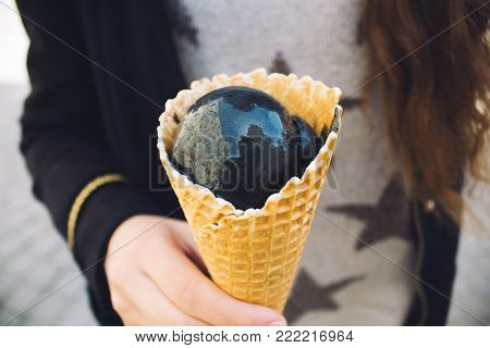 Trendy food. man hold a cone of charcoal black ice cream as background.