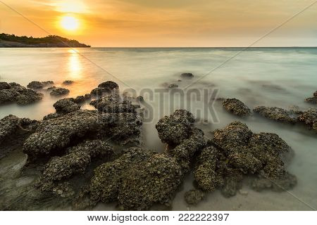 Stone In Sea And Wave On Sunset Time With Long Exposure At Ko Sichang District Chonburi, Thailand.
