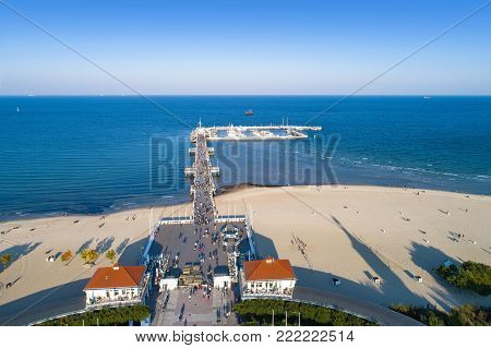 Sopot resort in Poland. Wooden pier (molo) with marina, yachts, beach, walking people, vacation infrastructure and promenade. Aerial view.