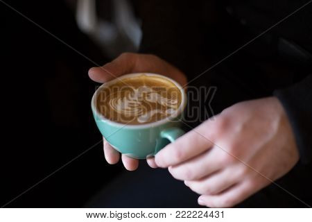 Woman holds cup with fresh coffee and funny horse blowing kiss latte art made with coffee.