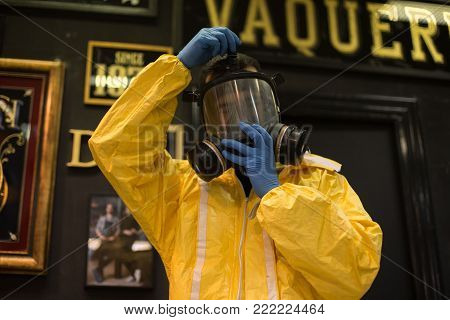 Professional artist or artisan craftsman, wears protection yellow suit and gas mask, for air filtering before painting or spraying with paint and dangerous chemicals
