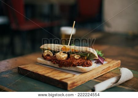 Fatty and savory unhealthy snack, pulled pork sandwich or toast with meat baked and spiced added to it. Served on wooden board with tap beer for lunch