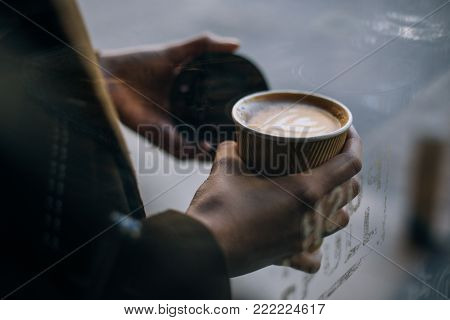 Fashionable woman in coat, stands outdoors on street, holds in hand with tattooed fingers, take away cup with coffee to go. Vintage look and feel nostalgia photo, tender and sensual morning routine
