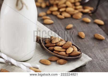 Whole almonds in a wooden spoon over a rustic table with a glass bottle of almond. Extreme shallow depth of field with selective focus on nuts in spoon.