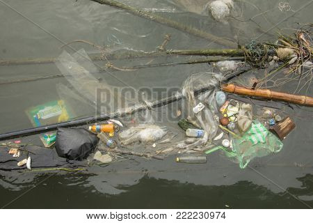 SANDAKAN, MALAYSIA - 14 JANUARY 2018: Pollution environmental problem. Plastic bags and bottles on beach beside ocean due to no recycling or refuse disposal.