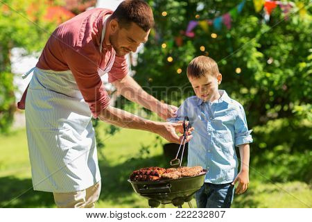 food, people and family time concept - father and son cooking meat on barbecue grill at bbq party in summer garden