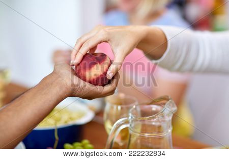 food, fruit and healthy eating concept - multiracial couple hands with peach