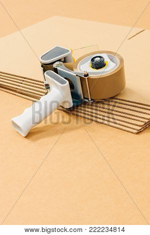 Industrial flat pack cardboard boxes or cartons with a generic tape gun a commercial packaging or despatch concept