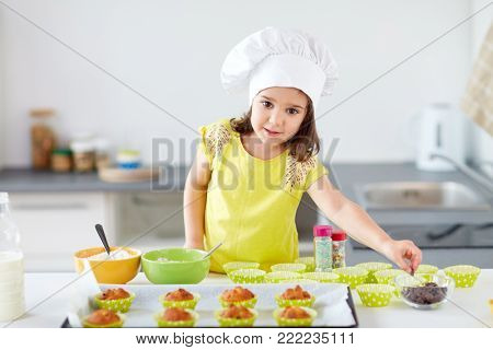 family, cooking and people concept - little girl in chefs toque baking muffins or cupcakes with chocolate sprinkles at home