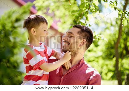 family, fatherhood and people concept - happy father and son at summer garden