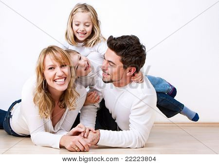 sweet young family having fun on the floor in their home