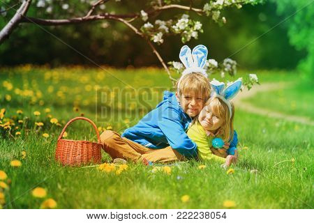 cute happy little boy and girl on easter eggs hunt in spring nature