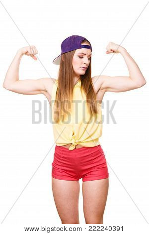 Woman casual style teen girl cap on head showing off muscles biceps. Youth style. Power and strength concept. Studio shot isolated on white