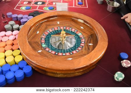Casino spinning wooden roulette wheel on a red felt table with chips on the side for gambling