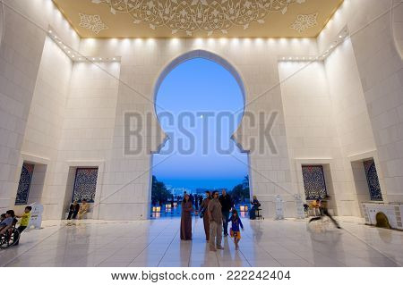 ABU DHABI, UNITED ARAB EMIRATES - DEC 31, 2017: The main hall and entrance of the Sheikh Zayed Mosque in Abu Dhabi in twilight. It is the largest mosque in the country.
